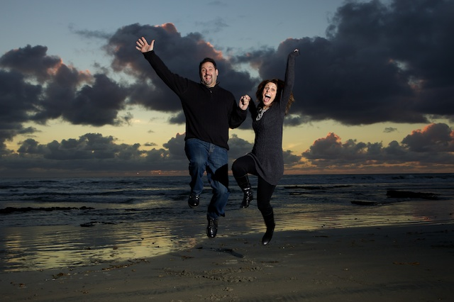 couple jumping in the air at the beach by Spark Photography