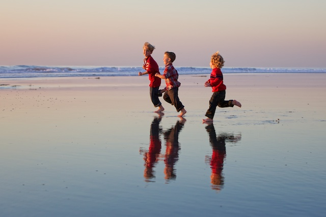 three boys running on the beach family photography